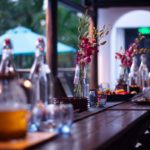 A photograph of a long table set out with iced-tea, fruit platter and flowers at the Gratitude Vietnam Yoga Retreat Venue for hire, Vietnam